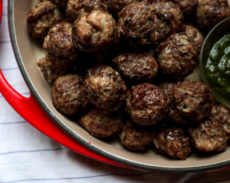 baked meatballs in a red dish with pesto on the side